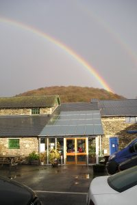 A double rainbow arching over the Café with Craggy Woods in the background