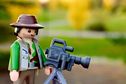A lego film maker standing behind a camera on a tripod